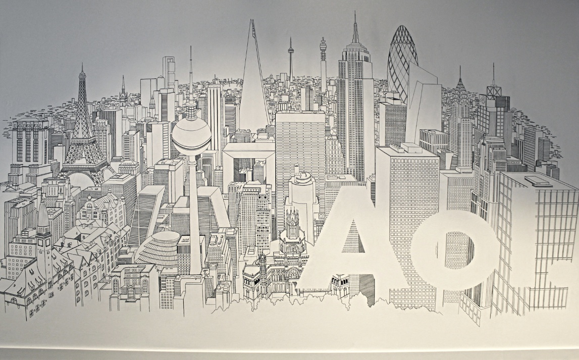 Renowned artist unveils cityscape mural at london hq for Black and white london mural wallpaper