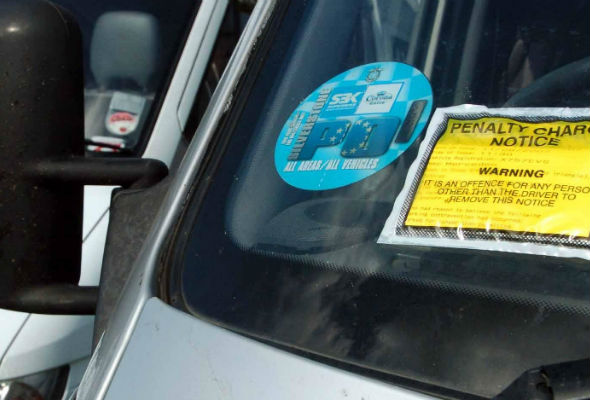 Traffic warden hands out ticket to van that was overhanging yellow lines by one inch