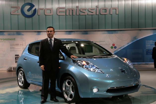 Carlos Ghosn stands next to a blue 2011 Nissan Leaf