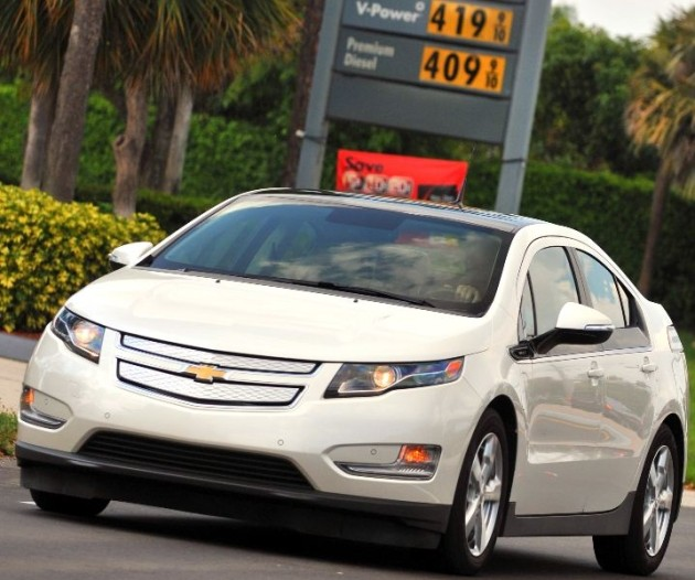 2011 Chevrolet Volt in front of gas sign