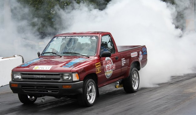 1989 Toyota Tacoma converted to electric, creates a cloud of tire smoke on a drag racing strip.