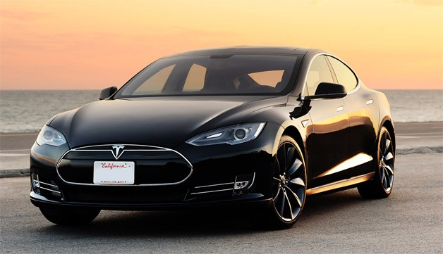 Black Tesla Model S at sunset with ocean in background.