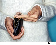 Woman looking at cash in purse