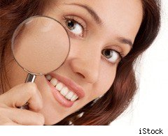Woman holding magnifying glass to skin