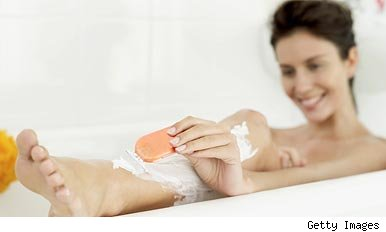 Woman shaving her legs in the bath