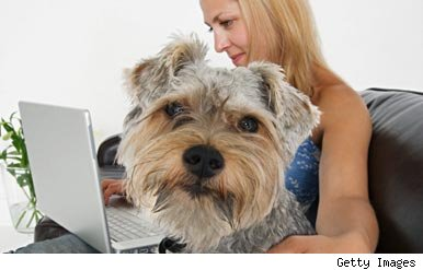 Woman using laptop with dog