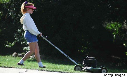 Young woman pushing a lawnmower