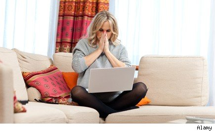 woman reacts to mistake as she sits on couch with laptop