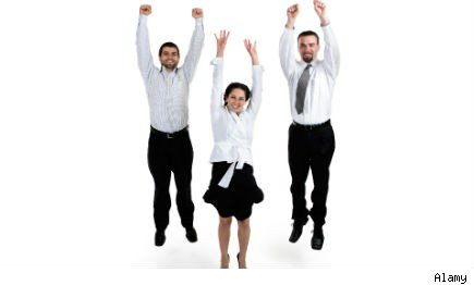 two men and a woman in business attire jumping for joy
