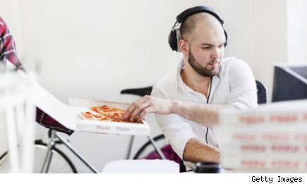 man at computer eats pizza from takeout box