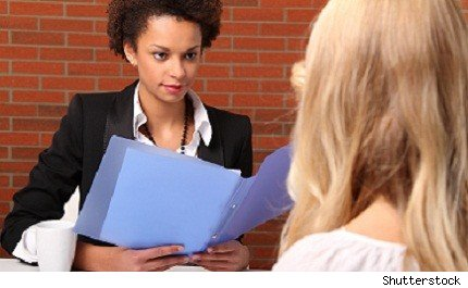 job interviewer holding resume as she interviews candidate
