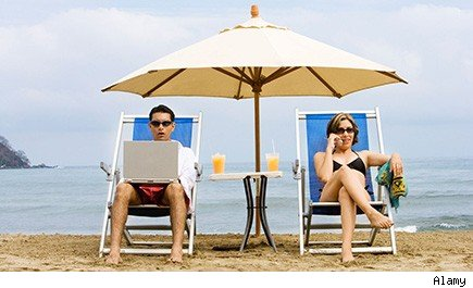 at beach, man works on laptop, woman talks on cellphone