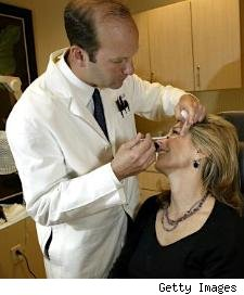 Doctor administering botox injections to a middle aged woman