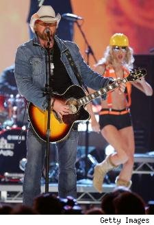 Toby Keith on stage with costumed backup singer