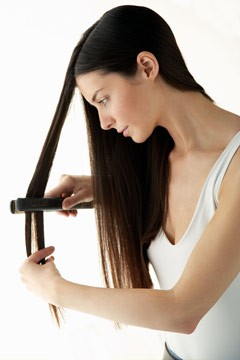 woman using flat iron