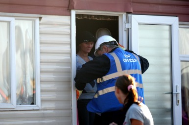 Bailiffs entering a mobile home