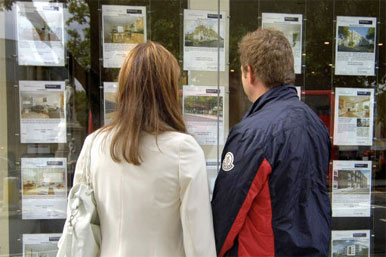 couple viewing estate agent's window