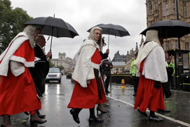 judges crossing road under umbrellas