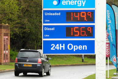 car driving past petrol price sign showing 156.9