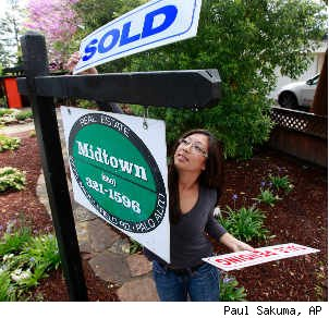 Real estate agent hanging sold sign