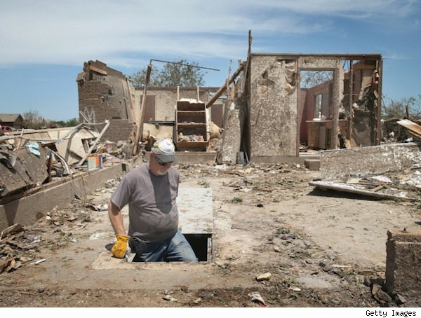 Man in opening of storm shelter surrounded by building rubble.