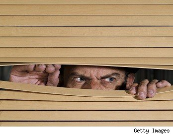 Angry man peering through blinds