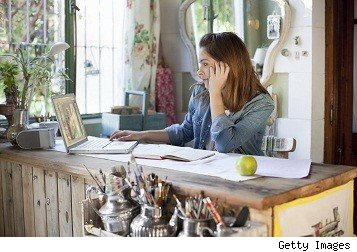 woman working in home office, looking at her laptop