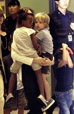 Which celebrity is hiding behind her children at the airport?