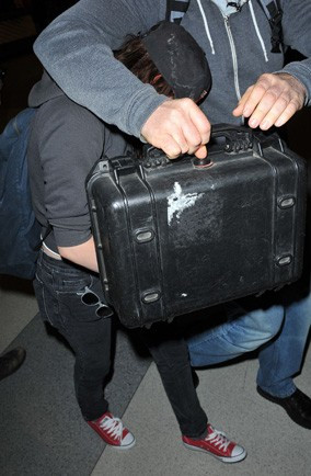 Can you guess who is hiding under their bodyguard at JFK Airport?