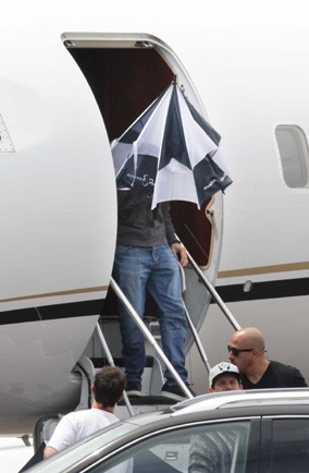 Which actor is hiding inside an umbrella while leaving his jet?