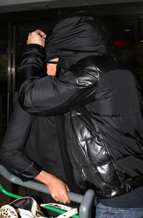 Who's the couple having an undercover kiss at Heathrow Airport?
