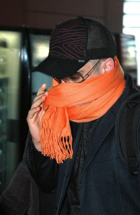 Can you guess which star is concealing his face with an orange scarf at Heathrow?