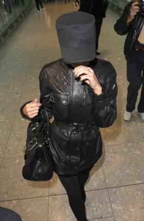 Which famous fashion designer used her hat to cover her face at Heathrow Airport?