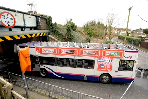 Double decker bus roof ripped off in railway bridge crash