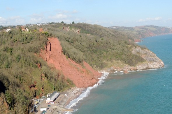 'Reckless' tourists climbing 150ft landslide to see collapsing house on Devon beach