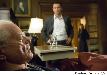 Christian (Julian McMahon) looks on as Burt Landau (Larry Hagman) recovers.