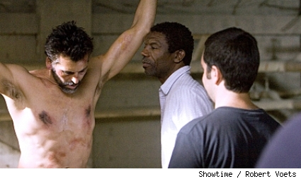 Oded Fehr (Farik) listens to episode director Vondie Curtis-Hall on the set of the Saudi prison.