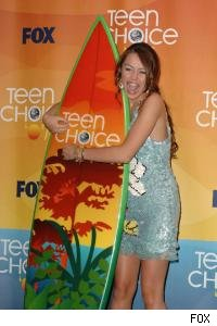 Miley Cyrus hugs a surfboard. 
