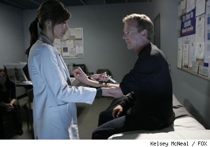 Dr. Macer (Christina Chang, L) treats Jack (Kiefer Sutherland, R) to mask his escalating symptoms.