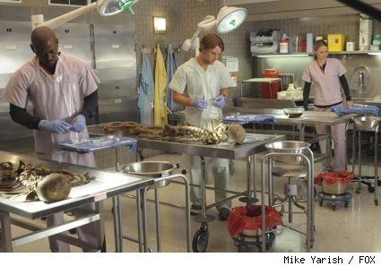 (L-R) Foreman (Omar Epps), Chase (Jesse Spencer) and Cameron (Jennifer Morrison) run tests on the skeletal remains of the father and grandfather of a patient who believes he's inherited an illness that kills the men in his family at age 40 in the HOUSE episode 'Brave Heart.'