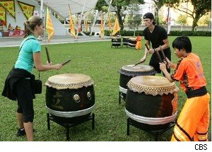A local boy teaches Caite and Brent the drums