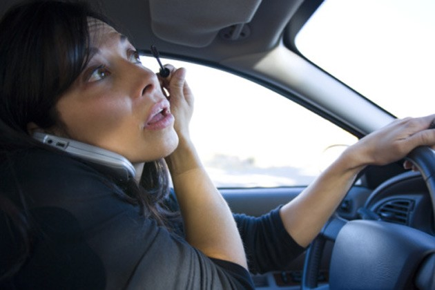 Distracted driver on phone, applying mascara