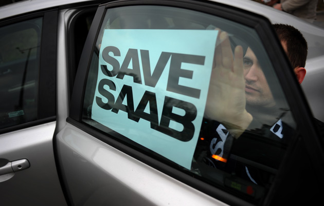 Man affixes 'Save Saab' sign to car window