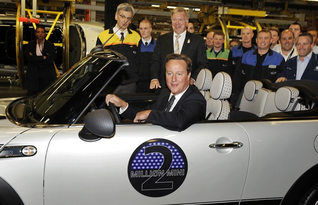 british prime minister david cameron drives the two-millionth mini cooper off the line