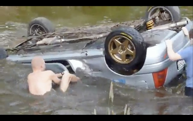 Rally spectators struggle to free drivers from submerged Renault Clio rally car