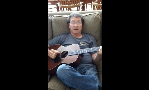 Country musician Mac davis playing guitar on couch