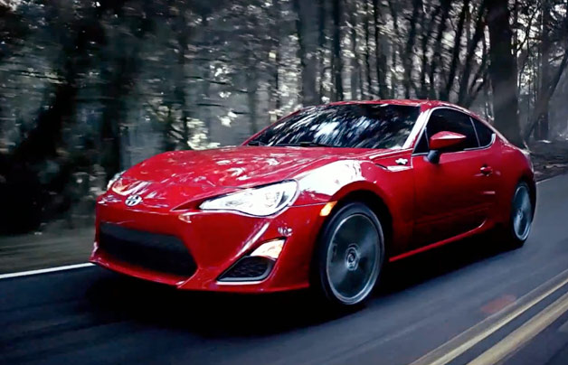 2013 Scion FR-S in red, front three-quarter dynamic screencap from first ad