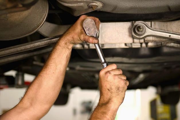 Auto mechanic turning a wrench under a vehicle