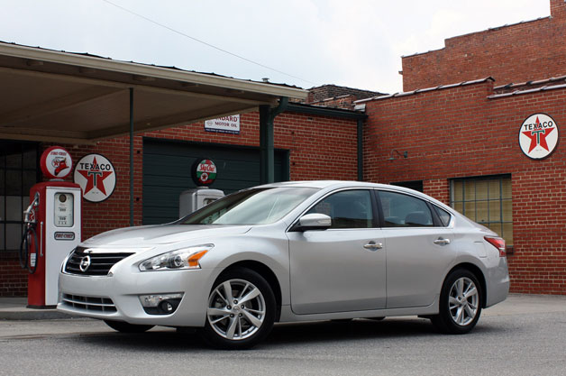 2013 Nissan Altima - silver - front three-quarter view parked in front of antique gas pumps
