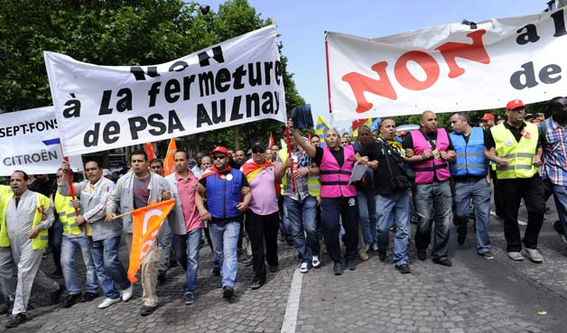 French workers protest Peugeot layoffs outside of company headquarters